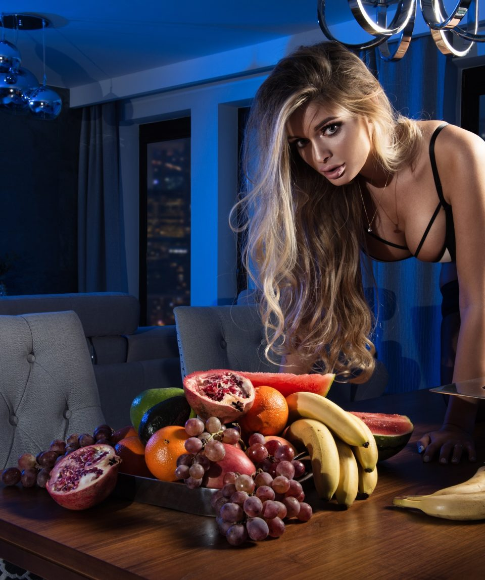 Sexy blond woman with fruits in dark room