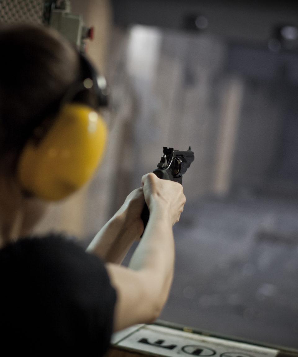 girl pointing gun on shooting range